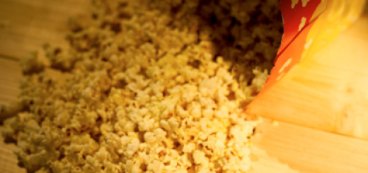 77006438-popcorn-spilling-from-container-onto-wooden-gettyimages